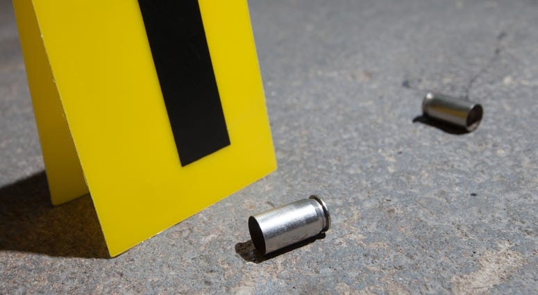 Evidence marker next to two empty handgun cartridges on concrete