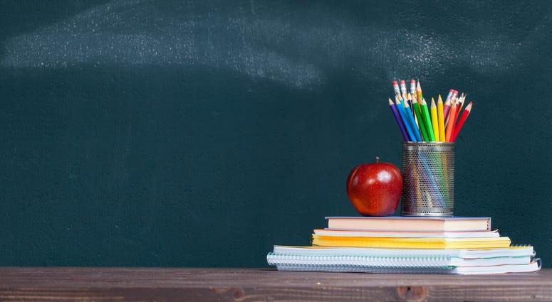 Pencil tray and an apple on notebooks on school teacher's desk