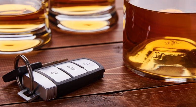 Car keys, several glasses and a bottle of whiskey or alcohol