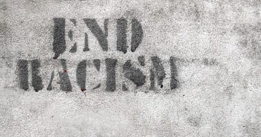 Graffiti on brick wall reads END RACISM
