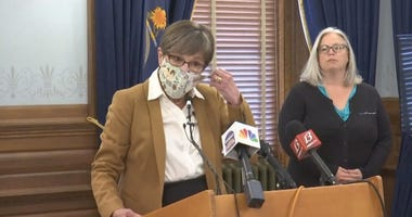 Governor Laura Kelly removes a face mask before beginning a news conference in Topeka, Monday, June 29, 2020.
