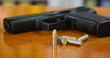 .38 mm handgun and bullets strewn on the rustic wooden table background