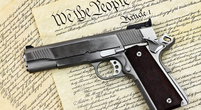 """Handgun lying over a copy of the United States constitution with the words """"We the People"""" visible."""
