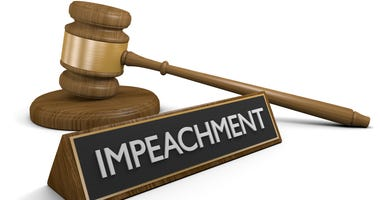 Law concept of a wooden court gavel next to a sign labeled impeachment