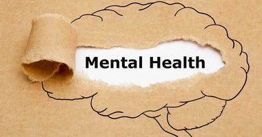 Mental Health appearing behind torn brown paper with drawn human brain on it