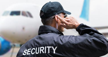 Rear view of mature security guard listening to earpiece