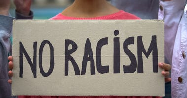 Girl holds sign reading 'No racism'