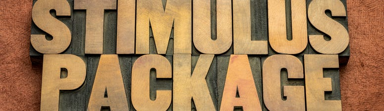 stimulus package word abstract in vintage letterpress wood type against textured handmade paper
