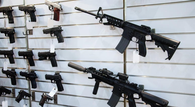 Gun wall rack with rifles and pistols