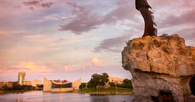 A view of the Arkansas River in Wichita, with the Keeper of the Plains in the foreground and Exploration Place behind it