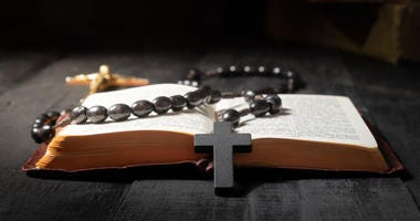 Flat lay image of New Testament, cross and rosary
