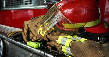Firefighter protection gear, helmet, gloves on the bumper of the fire truck