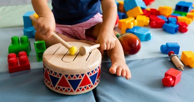 Little boy playing with wooden toy drum
