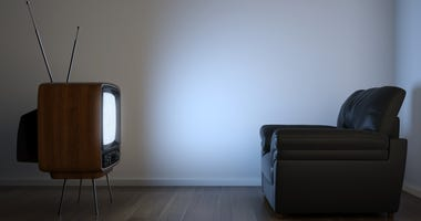 Side view of retro TV and black couch in an empty white room
