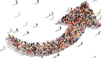 Large group of people in the shape of an arrow pointing up symbolizing direction , progress or growth