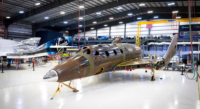 Virgin Galactic Wednesday, Jan. 8, 2020, shows Virgin Galactic's next passenger spaceship standing on its landing gear in what is known as a weight-on-wheels test, in a hangar at the company's Mojave Air & Space Port in Mojave, Calif.