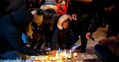 Mourners place candles and photographs outside the Alberta Legislature Building in Edmonton, Alberta, Wednesday, Jan. 8, 2020, during a vigil for those killed after a Ukrainian passenger jet crashed, killing at least 63 Canadians, just minutes after takin