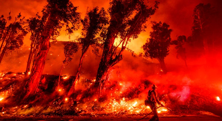 Flames from a backfire consume a hillside as firefighters battle the Maria Fire in Santa Paula, Calif. The decade that just ended was by far the hottest ever measured on Earth, capped off by the second-warmest year on record, NASA and the National Oceanic