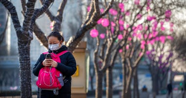 A woman wears a face mask as she walks along a street in Beijing, Wednesday, Jan. 29, 2020. China as of Wednesday has more infections of a new virus than it did in with SARS, though the death toll is still lower.