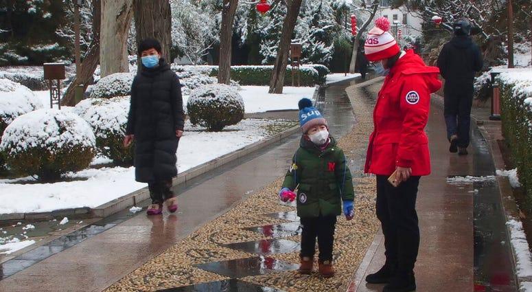 People wear face masks as they walk in public park on a snowy day in Beijing, Sunday, Feb. 2, 2020. T