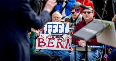 """A man with breathing tubes holds up a sign that reads """"Feel the Bern"""" as Democratic presidential candidate Sen. Bernie Sanders, I-Vt., left, speaks at a campaign stop at the Bernie 2020 Cedar Rapids Field Office, Sunday, Feb. 2, 2020, in Cedar Rapids, Iow"""