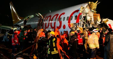 Rescue members and firefighters work around the wreckage of a plane after it skidded off the runway at Istanbul's Sabiha Gokcen Airport, in Istanbul, Wednesday, Feb. 5, 2020.