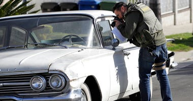 A member of the Los Angeles Sheriffs Dept. photographs a vehicle during an investigation outside of a home in connection with a cold case Wednesday, Feb. 5, 2020, in Los Angeles.