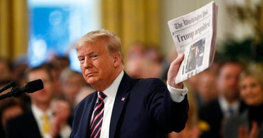 "President Donald Trump holds up a newspaper with the headline that reads ""Trump acquitted"" as he speaks in the East Room of the White House in Washington, Thursday, Feb. 6, 2020."