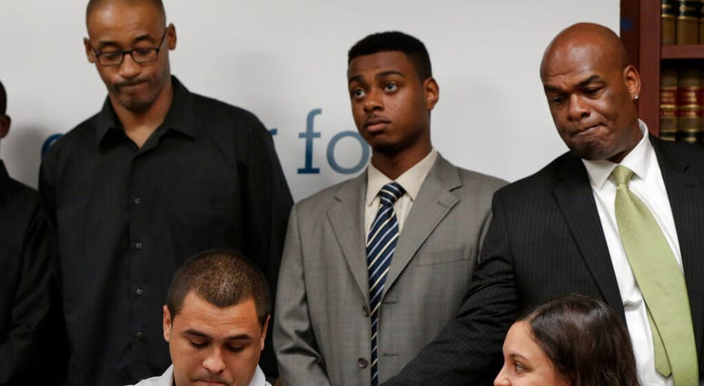 David Ourlicht, seated left, is comforted by Merault Almonar, standing at right, father of plaintiff Devin Almonar,