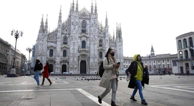 A woman wearing a sanitary mask walks past the Duomo gothic cathedral in Milan, Italy, Sunday, Feb. 23, 2020.
