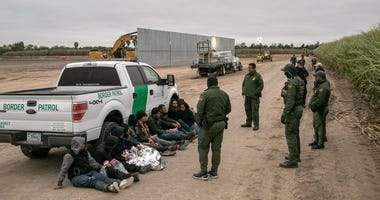 U.S. Border Patrol agents detain undocumented immigrants caught near a section of privately-built border wall under construction on December 11, 2019 near Mission, Texas.