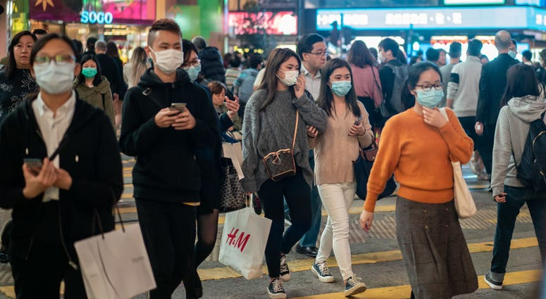 edestrians wear face masks as they walk through a crosswalk in Causeway Bay district on January 23, 2020 in Hong Kong, China.
