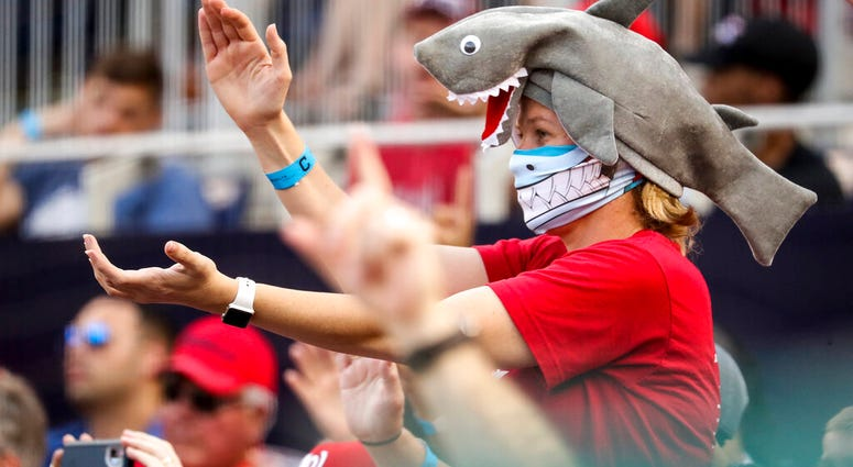 In this Sept. 29, 2019, file photo, a fan wears a shark hat as Washington Nationals' Gerardo Parra comes up to bat in the eighth inning of a baseball game against the Cleveland Indians at Nationals Park in Washington.