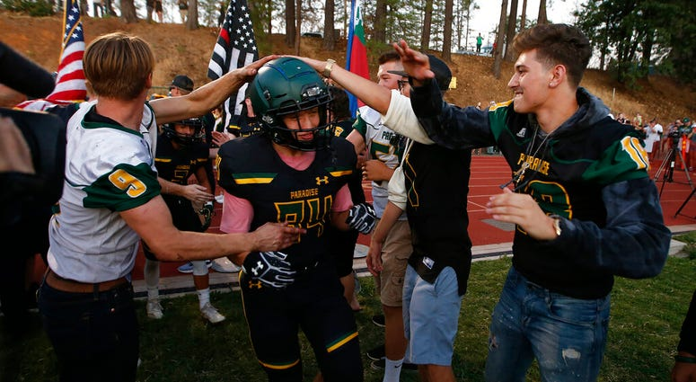 In this Aug. 23, 2019 file photo, Paradise tight end Jacob Duncan runs through a tunnel of former players during the opening ceremony of their high school football game against Williams, in Paradise, Calif.