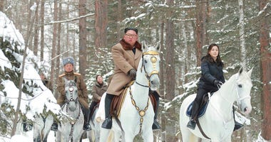 This undated photo provided on Wednesday, Dec. 4, 2019, by the North Korean government shows North Korean leader Kim Jong Un, center, with his wife Ri Sol Ju, right, riding on white horse during his visit to Mount Paektu, North Korea.