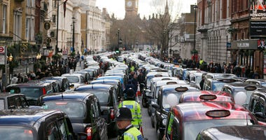 In this Wednesday, Feb. 10, 2016 file photo, London taxis block the roads during a protest in central London, concerned with unfair competition from services such as Uber.