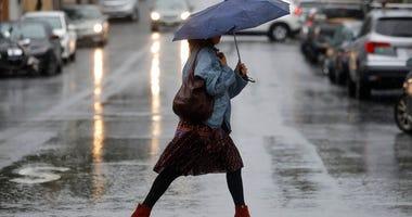 A woman carries an umbrella while walking in the rain in San Francisco, Tuesday, Nov. 26, 2019.