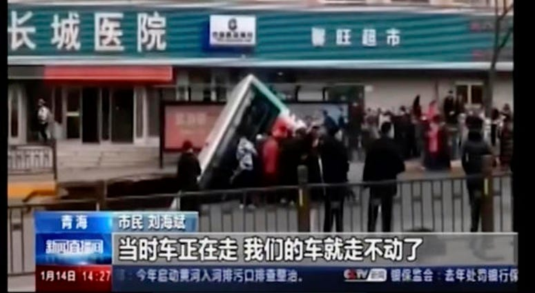 CCTV video, a bus plunges into a sinkhole in the center of a downtown street, Monday, Jan. 13, 2020, in Xining, Qinghai province, China.