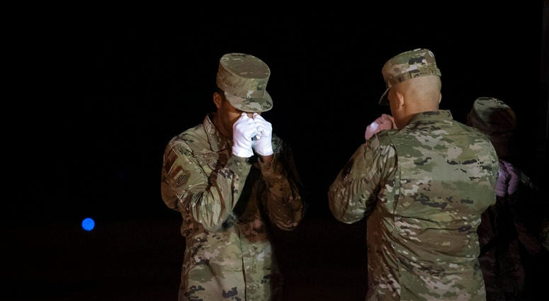 An Air Force carry team pays respect after moving a transfer cases containing the remains of Ensign Cameron Joshua Kaleb Watson, Seaman Mohammed Sameh Haitham and Seaman Apprentice Cameron Scott Walters, Sunday, Dec. 8, 2019, at Dover Air Force Base, Del.