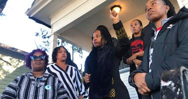 Sharena Thomas, left, Carroll Fife, center, Dominique Walker, second from right, and Tolani KIng, right, stand outside a vacant home on Magnolia Street in West Oakland, Calif.
