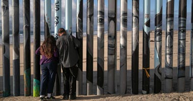 Faces of people deported from the United States adorn the U.S.-Mexico border fence on the beach on September 28, 2019 in Tijuana, Mexico.