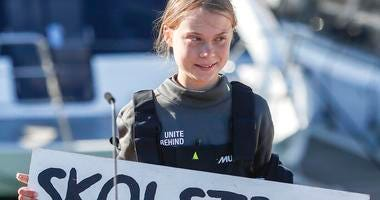 """Climate activist Greta Thunberg holds a """"Fridays for Future"""" banner in Lisbon, Tuesday, Dec 3, 2019."""