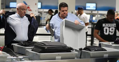 2 men at a TSA checkpoint at an airport
