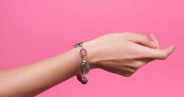 A woman's wrist on a pink background