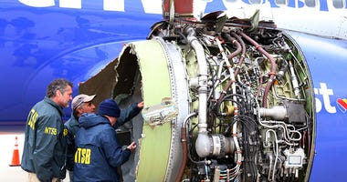 National Transportation Safety Board investigators examine damage to the engine of the Southwest Airlines plane that made an emergency landing at Philadelphia International Airport in Philadelphia on Tuesday, April 17, 2018. The Southwest Airlines jet ble