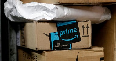 In this May 9, 2017, file photo, a package from Amazon Prime is loaded for delivery in New York. Last year, the online retailer introduced a system for letting people delivering packages into customers' homes. Now, it's their cars. GM says more than 7 mi