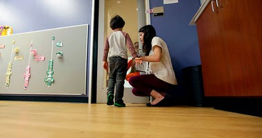 Megan Krail helps a 4-year-old boy with Autism