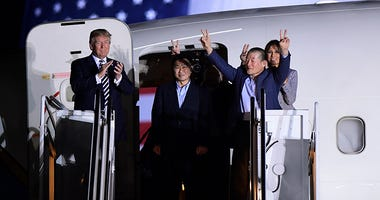 President Donald Trump, from left, greets Tony Kim, Kim Hak Song, seen in the shadow, and Kim Dong Chul, three Americans detained in North Korea for more than a year,