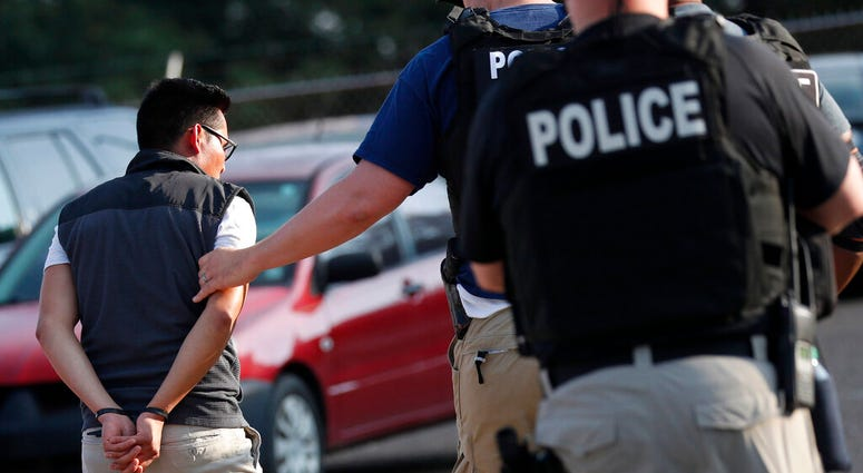 A man is taken into custody at a Koch Foods Inc. plant in Morton, Miss.
