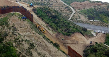 construction crews replace a section of the primary wall separating San Diego, above right, and Tijuana, Mexico, below left, seen from Tijuana, Mexico.